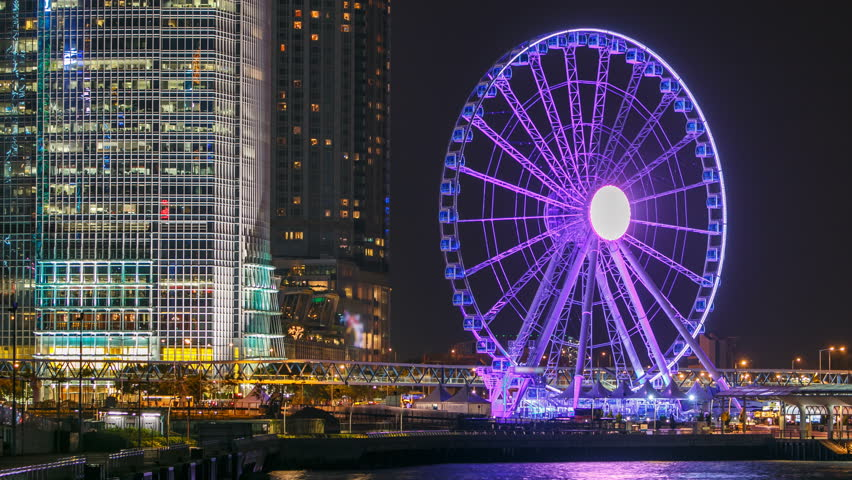 Skycrapers night timelapse and Hong Kong Observation Wheel, which is the latest tourist attraction in the city. close view with embankment and reflection on water. 4K | Shutterstock HD Video #14857852