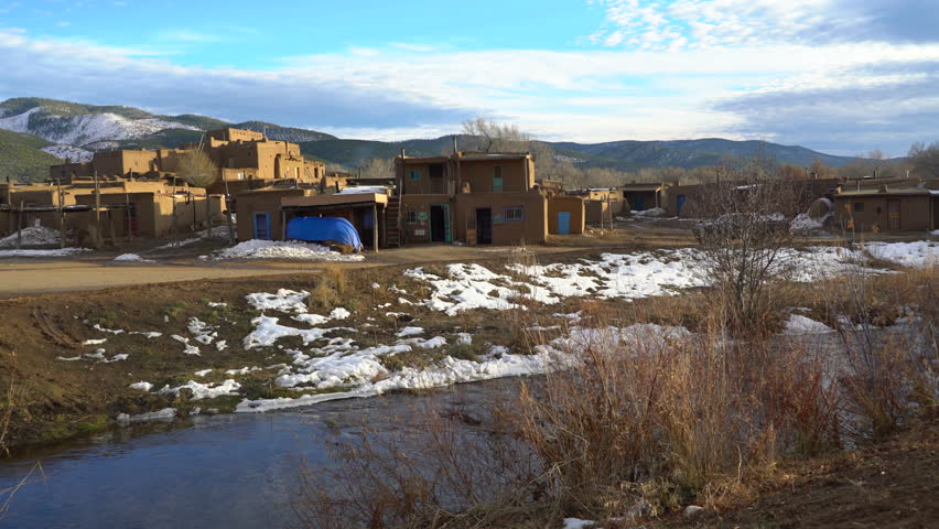 Footage with pan left motion of traditional Native American houses over river in Taos Pueblo, New Mexico