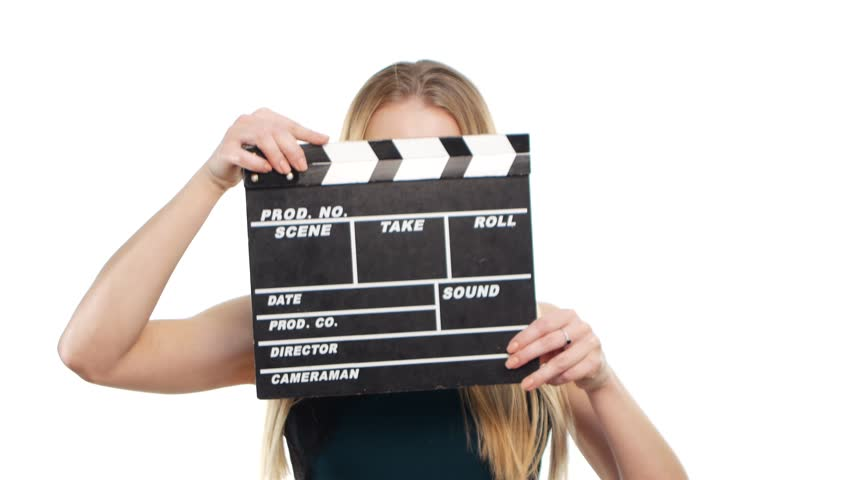 Elegant woman with sexy red lips using clapper board and smiling, on white