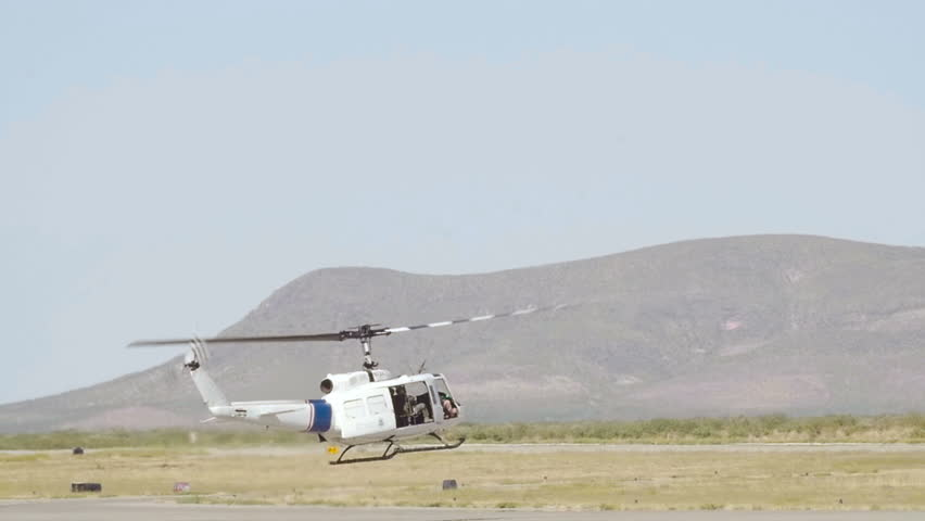 Slow motion shot of a helicopter flying at a low altitude near a small airport with mountains in the background. - HD stock footage clip