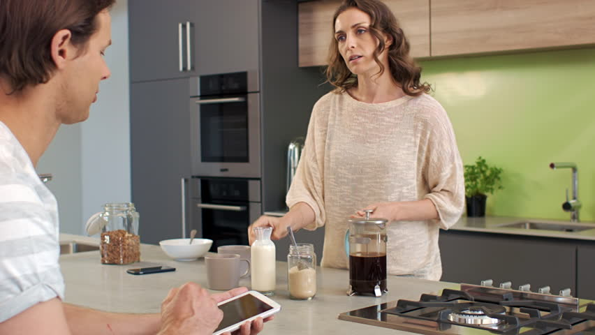 Husband and wife breakfast morning routine at kitchen counter, having coffee on their devices - HD stock video clip