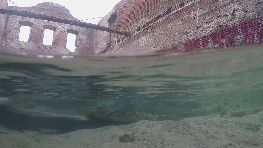 Underwater split: beautiful pure fresh water waterfall flowing from old destroyed house. - HD stock video clip