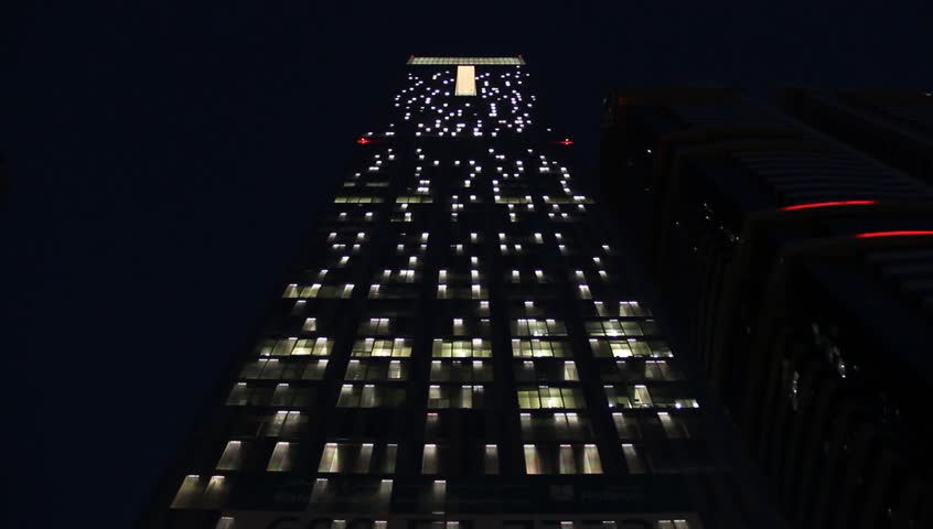 Look up to illuminated checkered tower facade at night. Lights turn on and off, slow random flick around whole wall. Dark outdoors, black sky on background. #14928322