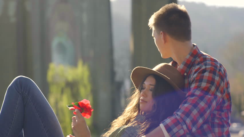 Attractive Young Couple Relax In Park, Take Turns Smelling A Flower - 4K stock video clip