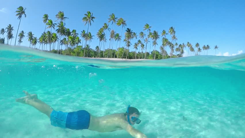 SLOW MOTION UNDERWATER CLOSE UP: Happy young man swimming under the water surface in picture perfect turquoise blue lagoon ocean at tropical island with exotic white sandy beaches in sunny summer