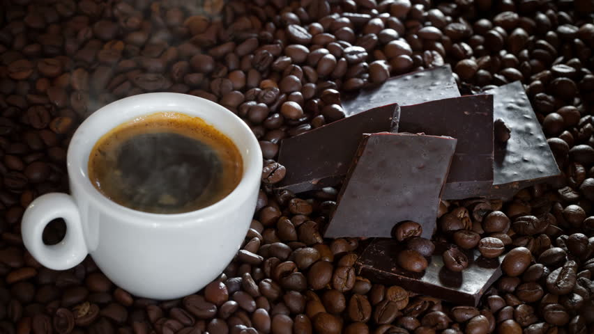 Espresso coffee and dark chocolate on coffee beans background.