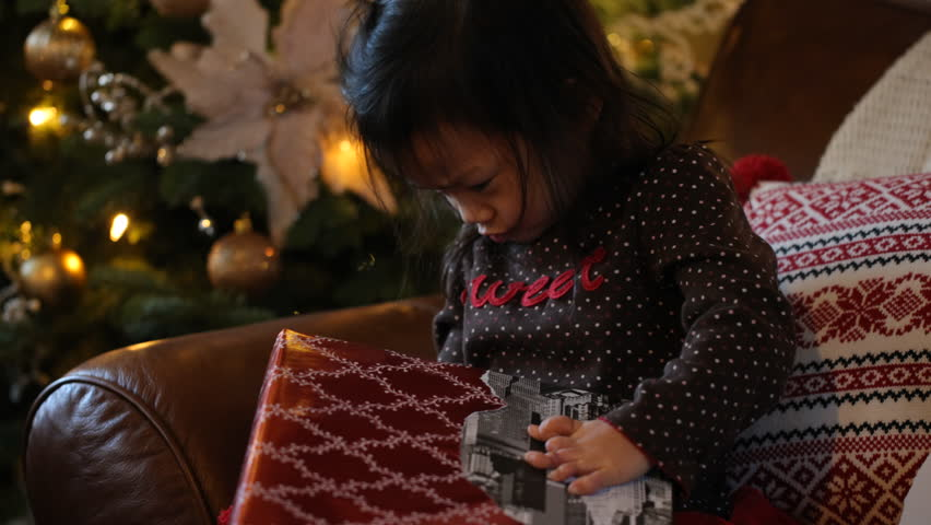 Young girl opening gift at Christmas
