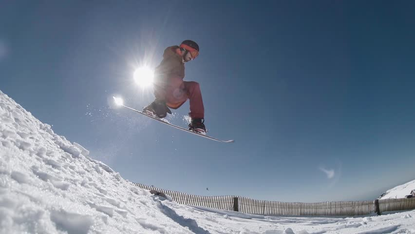 Snowboarder executing a radical jump against blue sky. | Shutterstock HD Video #15034405