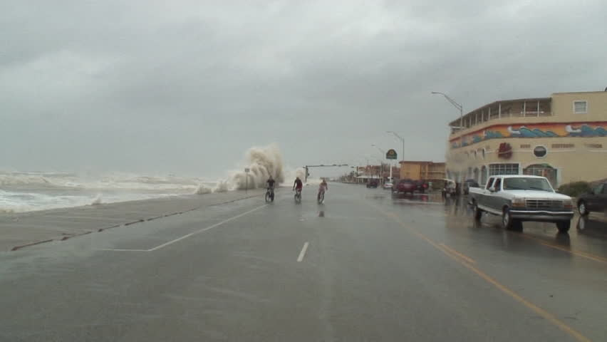Hurricane Storm Surge hits a seawall and knocks down two cyclists hard