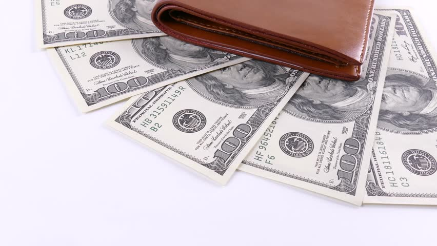 American currency and wallet on a white background