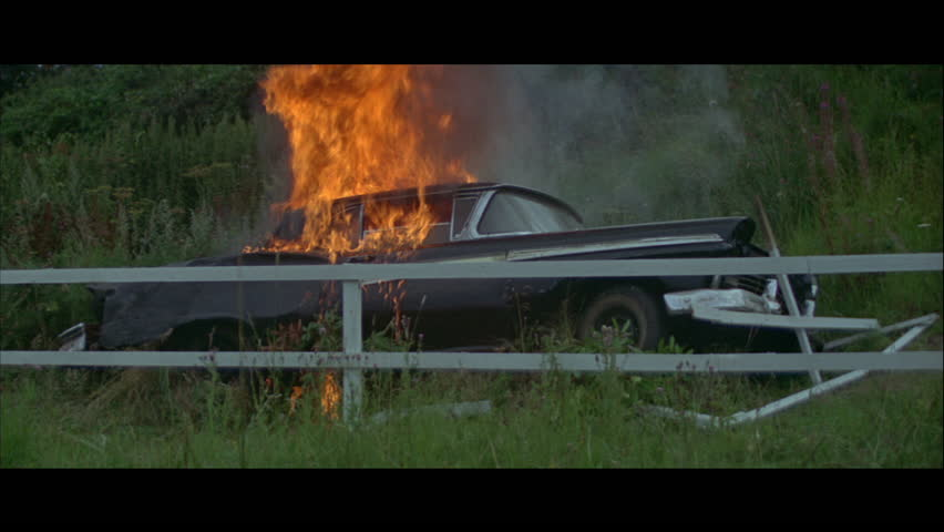 Fancy black car on fire and on its side in the countryside, 1965