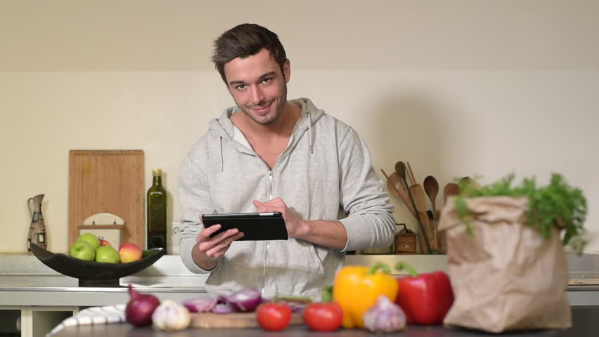 Young man cooking in kitchen at home with tablet - HD stock footage clip