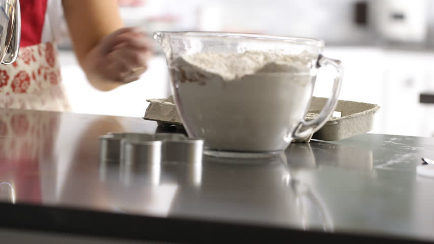 Scooping ingredients into electric mixer