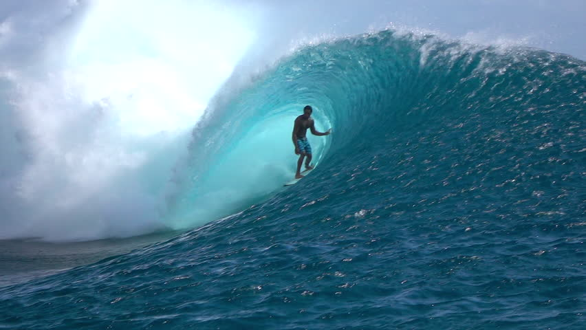 FPV SLOW MOTION: Cheerful extreme pro surfer surfing big tube barrel wave Teahupoo in crystal clear Pacific ocean in sunny Tahiti island