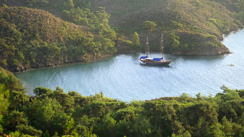Beautiful nature of Mediterranean on the azure coast of Turkey. 4K. Bordubet - a shallow bay surrounded by pine tree forest. Typical Turkish style gulet yacht anchored in the bay