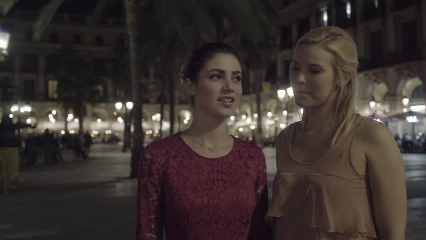 Young Adult Women at night visiting square in Barcelona and take selfie - 4K stock footage clip