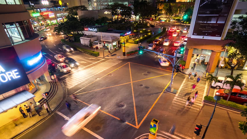 MAKATI, PHILIPPINES - 10 May 2015 Zoom out timelapse of intersection near Mall in Makati City, showing traffic moving by night. Makati is the business and financial center of metro Manila