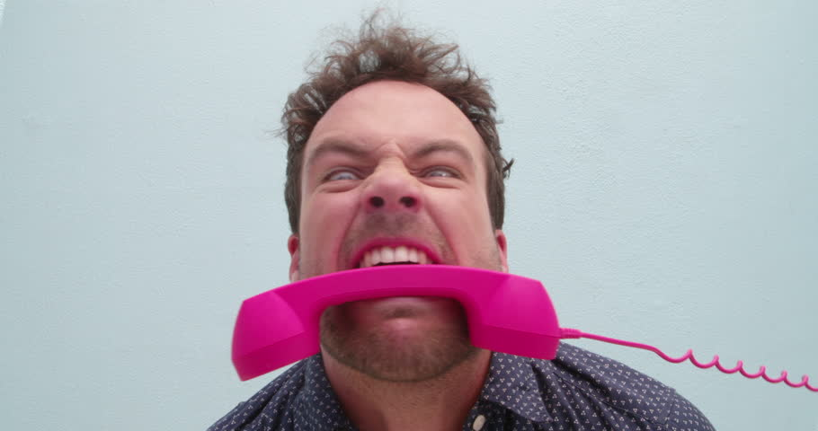 Young angry man holding telephone handset in his teeth, isolated on blue wall background | Shutterstock HD Video #15388069