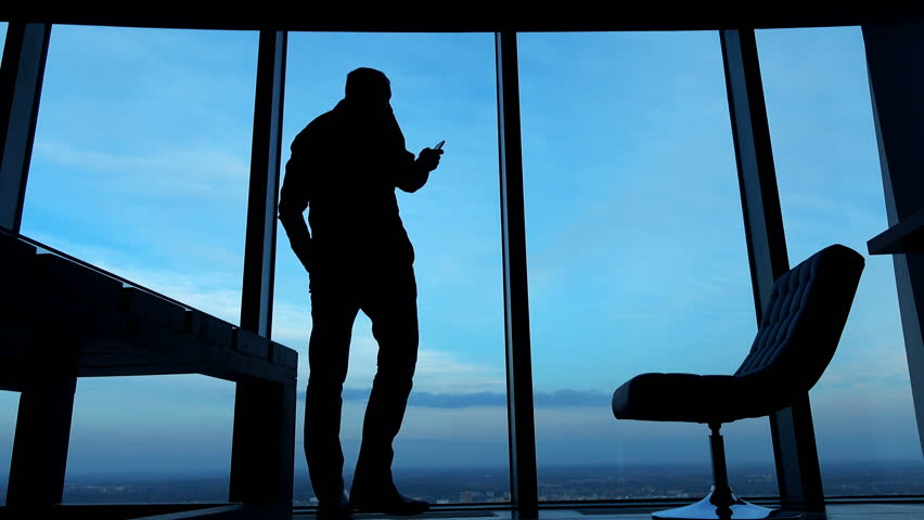 Silhouette of businessman standing with smartphone by window in the office against the sky in the evening, 4K