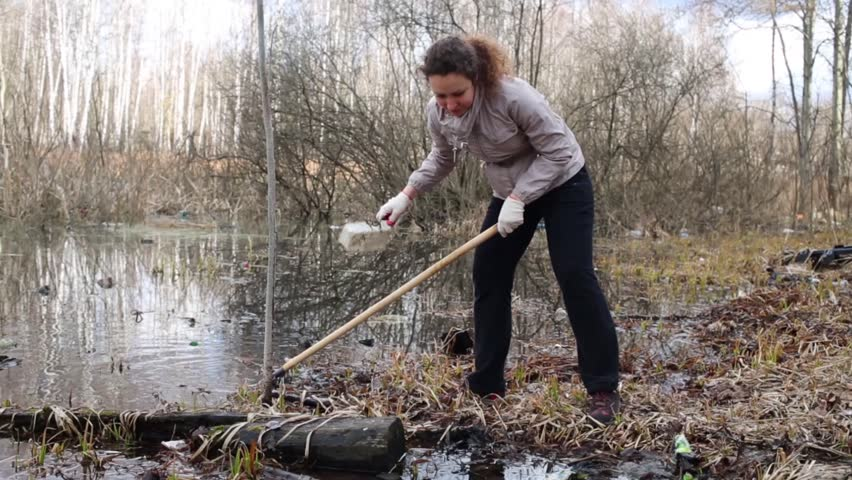 Woman pulls out garbage from water during spring cleaning of territory - HD stock footage clip