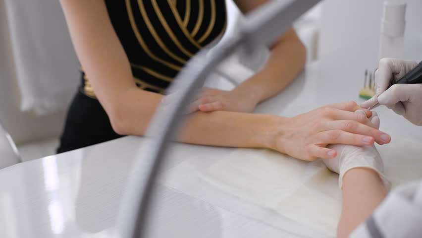 The master uses an electric machine to remove the nail polish on the hands during manicure in the salon.  - 4K stock footage clip