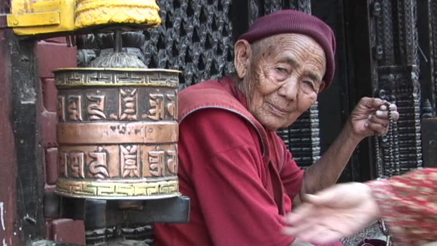 KATHMANDU, NEPAL - CIRCA 2005: Old Buddhist monk (or nun) with prayer beads next to spins prayer wheel circa 2005 in Kathmandu. - SD stock footage clip