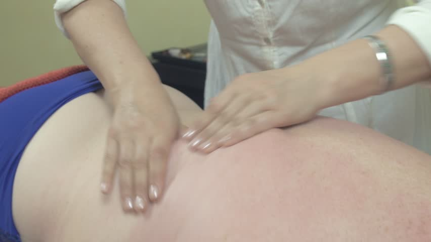 Masseuse make remedial massage of right back side to adult fat woman in saloon. Healthcare. Therapy. Close up - 4K stock video clip
