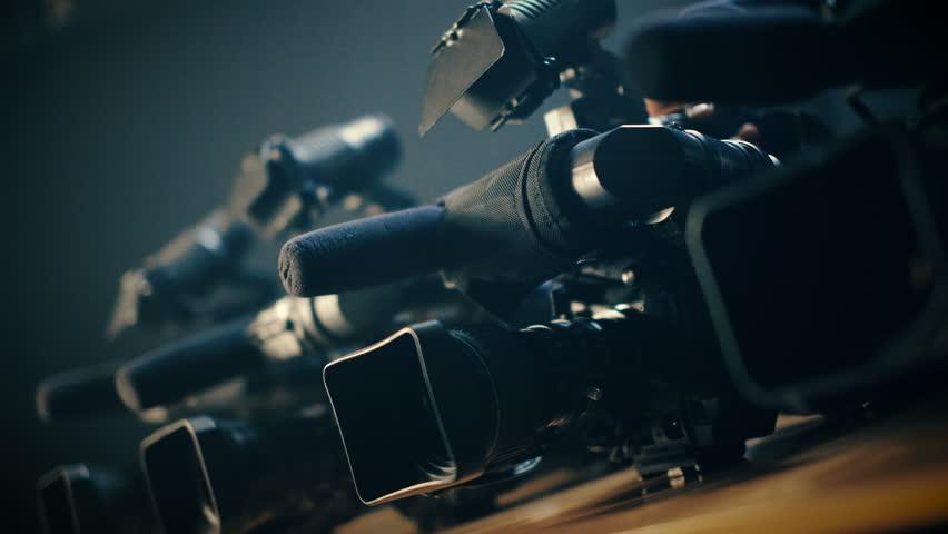 Cameraman prepares his professional  video camera for an urgent, rapid shooting