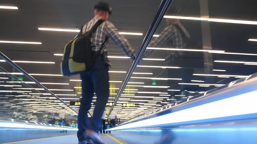 Man on escalator transportation to connection flight in airport