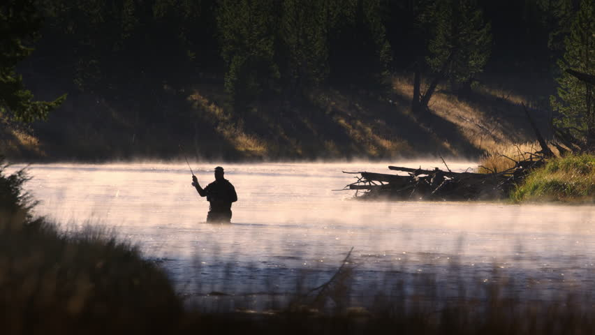 Silhouetted fly fisherman standing in the middle of scenic river.  Fishing line glinting in morning sunlight in slow motion. Yellowstone National Park, Wyoming and Montana, USA. 4K. | Shutterstock HD Video #15643111