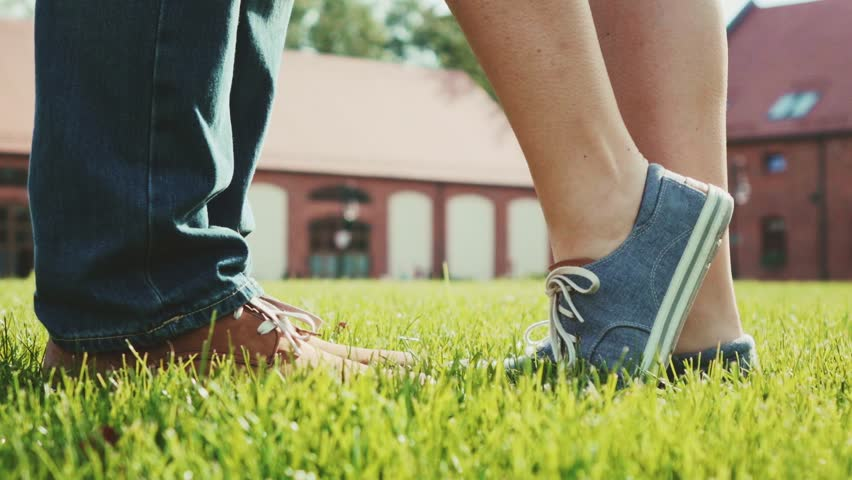 Close up of feet and legs as woman is tip toeing for a kiss. Romantic Couple kissing on a green grass lawn outdoors. Slow Motion 120 fps. Young love concept with lovers kissing. Stylish hipster shoes. #15651004