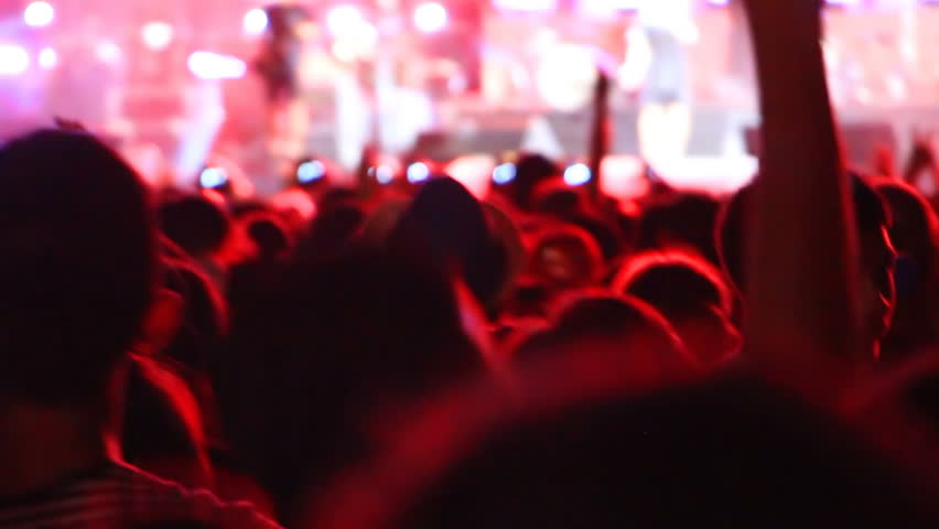 Crowd of young fans jumping at concert