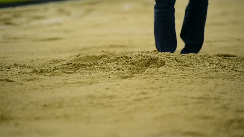 Athlete performing a long jump in the sand pit during athletics competition   Shutterstock HD Video #15684916