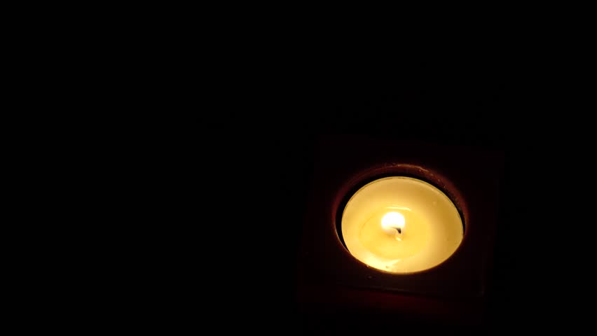 Tea light candle in the dark is blown out. - 4K stock video clip