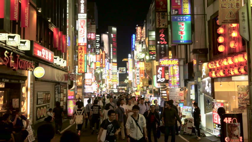 Tokyo - 15 MAY 2015: Static shot of people passing by resto and karaoke bars at night in Tokyo, the capital city of Japan on 15 May 2015 in tokyo Japan - 4K stock video clip
