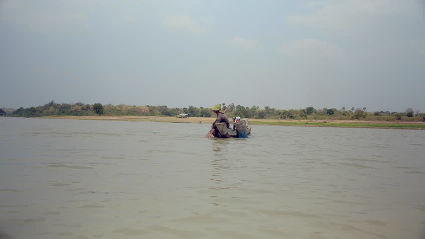 Fisherman pulling drop net out of the river, catching prawns and baiting net again for a new catch ( view from a boat)