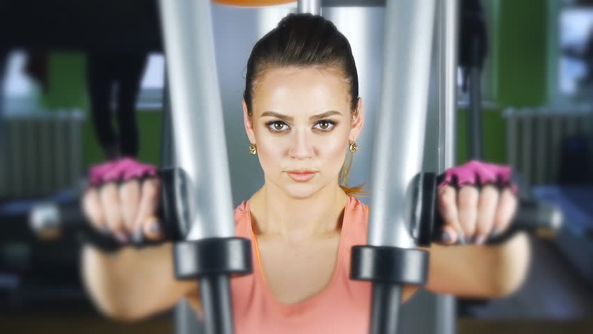 Woman doing fitness training on a butterfly machine with weights in a gym - HD stock video clip