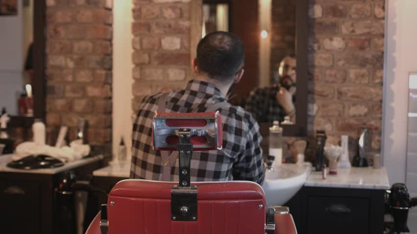 Portrait of Barber in Barbershop looking to camera