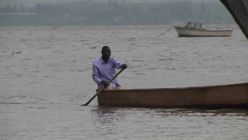 LAKE VICTORIA, UGANDA - CIRCA 2009: A man rows a fishing boat circa 2009 in Lake Victoria. - HD stock video clip