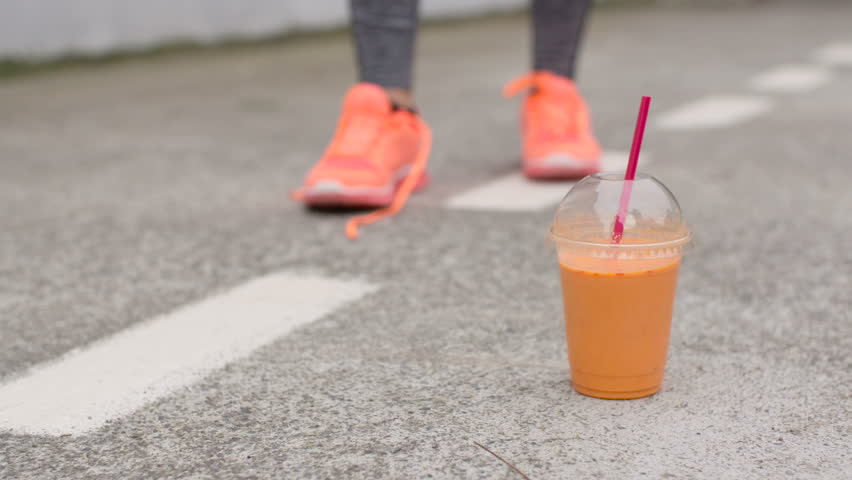 Female athlete picking up orange detox smoothie drink after lacing running footwear during urban outdoor workout.