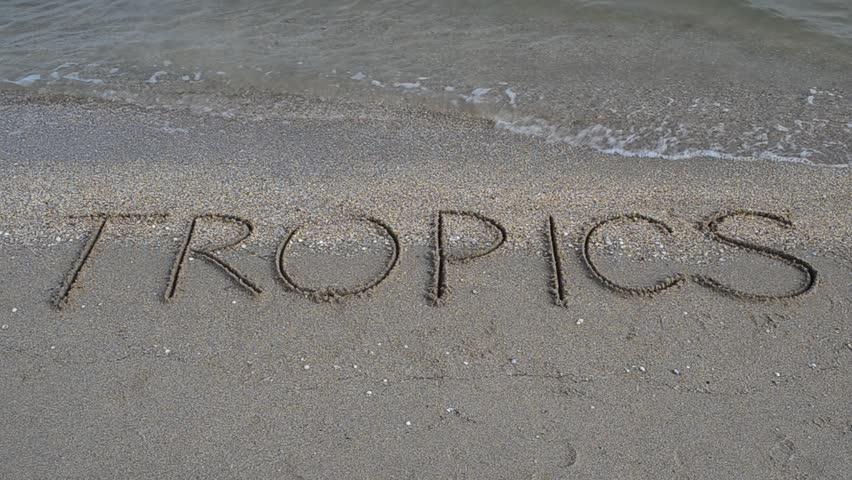 Inscription Tropics on sand on the beach. - HD stock video clip