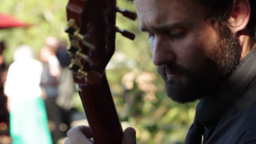 Close-up of man playing acoustic guitar outdoors at a dinner party in northern California. | Shutterstock HD Video #15847474