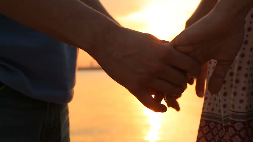 Man and woman holding hands at sunset. close-up of hands | Shutterstock HD Video #15868867