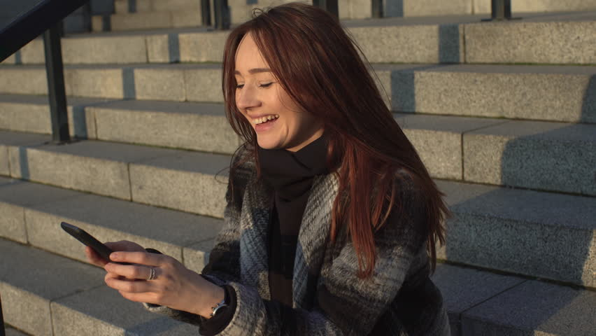 Girl Sitting on the Steps With a Telephone at Sunset, Photographs , Smiling , Sophisticated Technology , Urban Style , Brunette With Long Hair , a Gray Coat, a Sunny Day 4k | Shutterstock HD Video #15921724