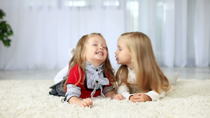 Sisters smiling while lying on the carpet. DOLLY HD  - HD stock video clip