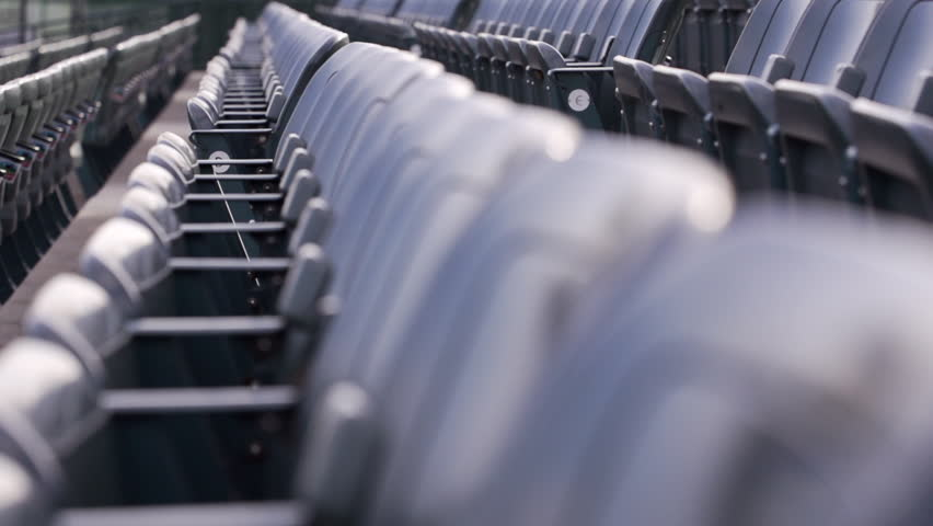 Slow motion dolly shot of empty stadium seats - HD stock footage clip