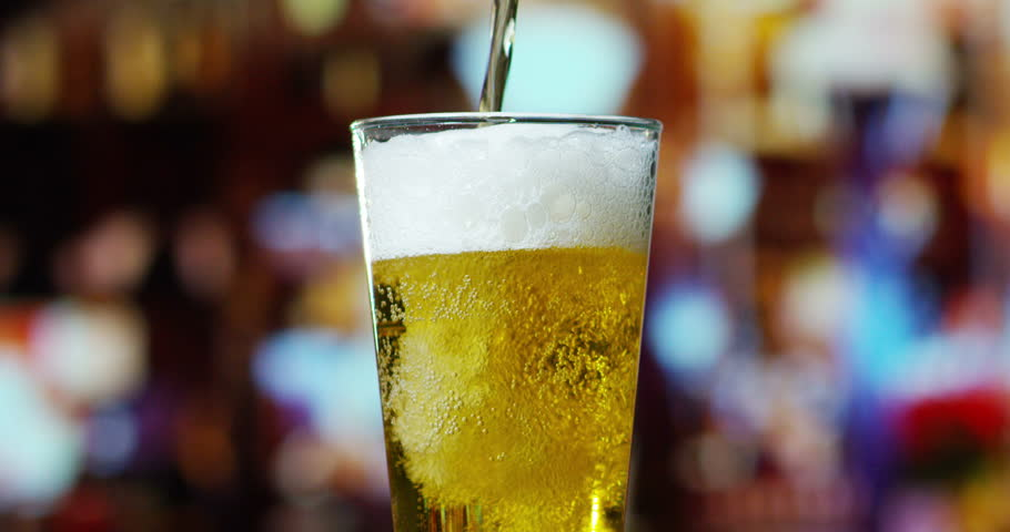Beer is pouring from the top into the glass forming waves | Shutterstock HD Video #15964762