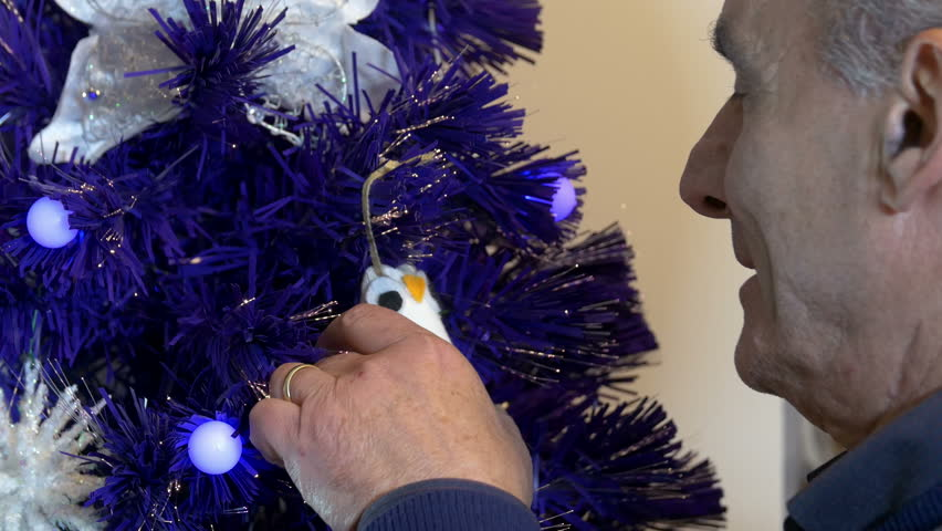 White retired man decorating a christmas tree, profile, touching - 4K stock video clip