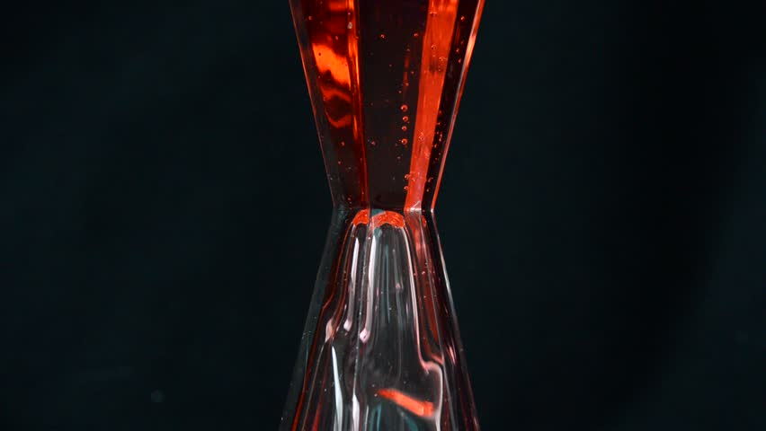 moving of red liquid in hourglass on black background - HD stock video clip