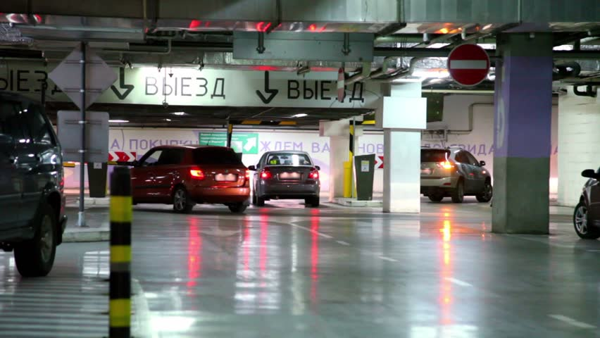 Several cars ride away from underground parking garage, automatic turnpikes let them go by one. Inscriptions on the walls: Drive exit, Thanks for purchase, wait for you again, Goodbye - HD stock video clip
